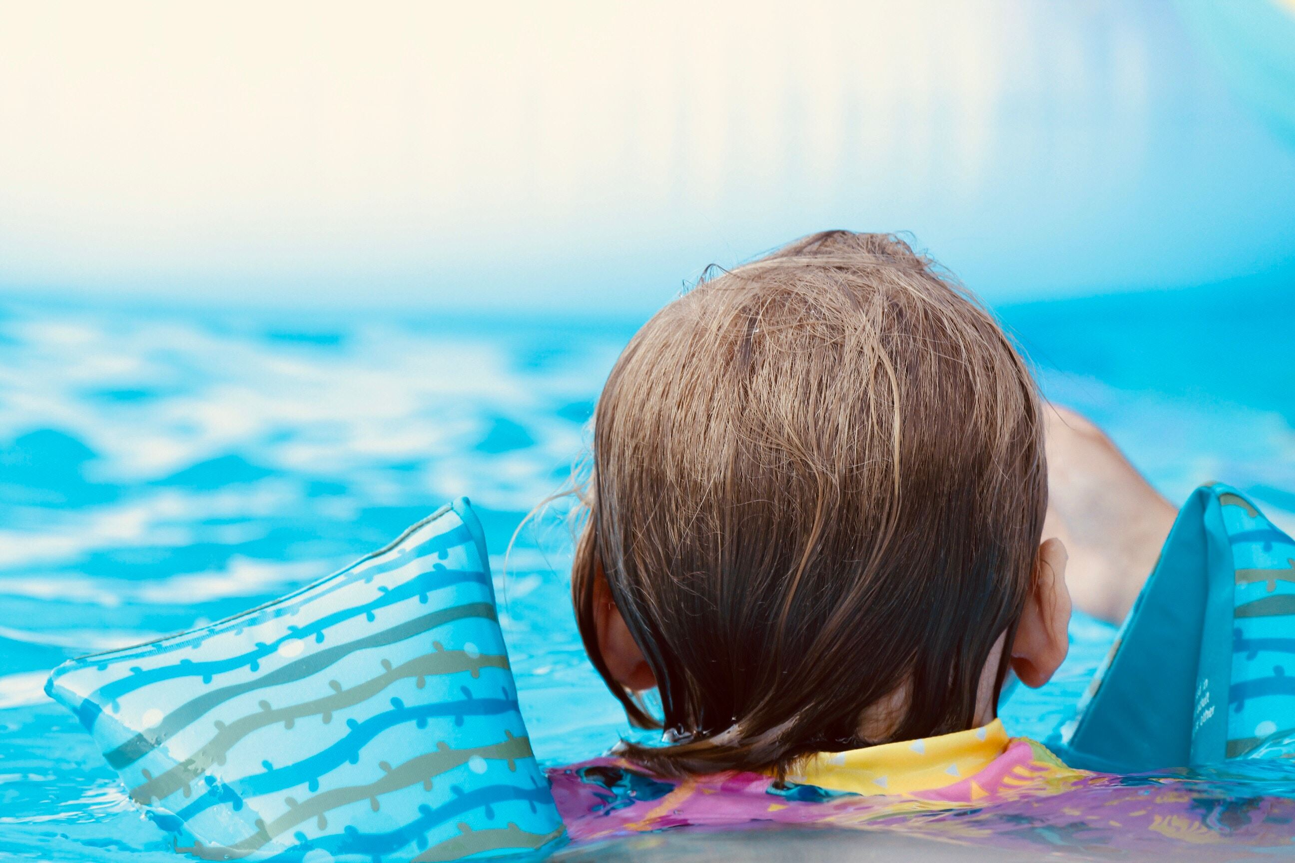 Photo of the back of a young child in a blue pool wearing inflatable arm bands.