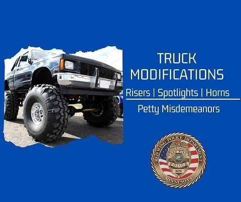 "Image of lifted truck with ""Truck Modifications Risers, Spotlights, Horns"" and RWPD seal on bl"