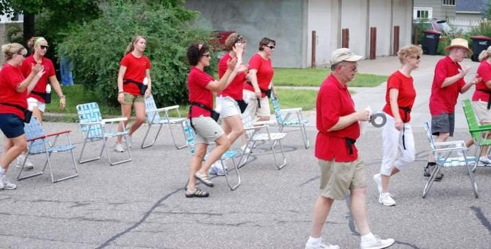 People in Red Shirts with Lawn Chairs in Parade