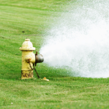 Photo of a yellow fire hydrant flushing water out over grass.
