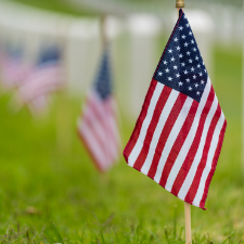 Close-up photo of a small American flag pushed into grass with other flags and memorial stones
